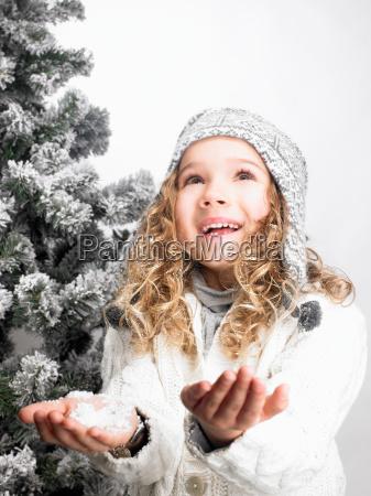 little girl next to a fir