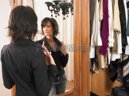 woman looking at herself in the