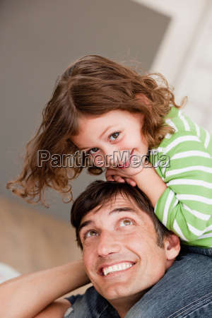 daughter riding on fathers shoulders