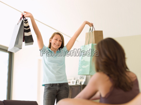 teenage girl showing shopping to mother