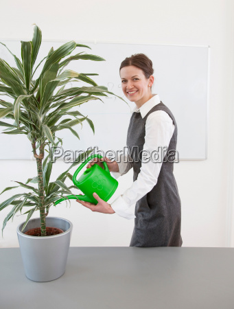 businesswoman watering plant