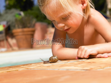 little girl looking at a snail