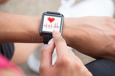 mano humana que usa reloj inteligente
