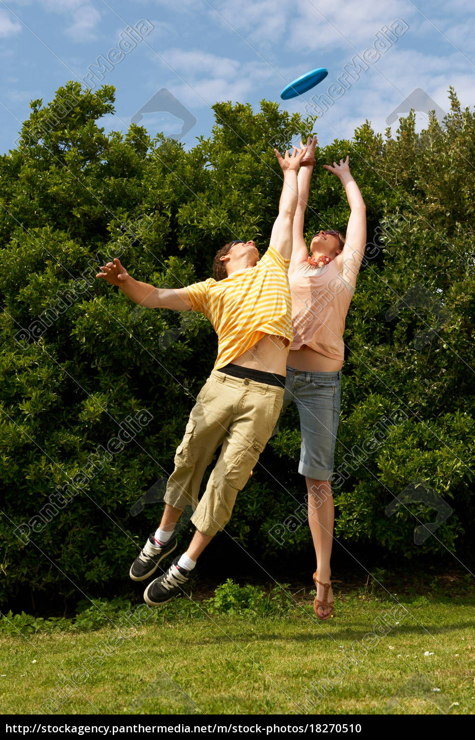 couple, jumping, to, catch, a, frisbee - 18270510