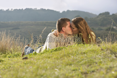young couple lying and kissing in