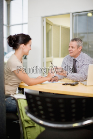 woman signing papers with car salesman