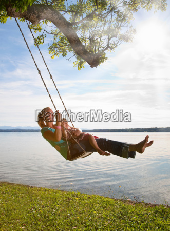 mother and daughter swinging from tree