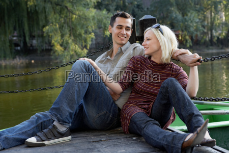 couple on a dock smiling and