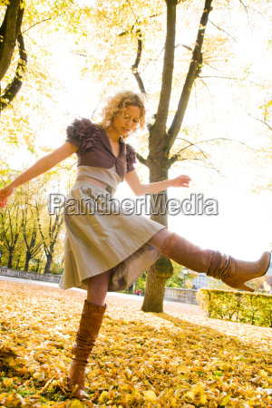 woman dancing within heaps of leaves