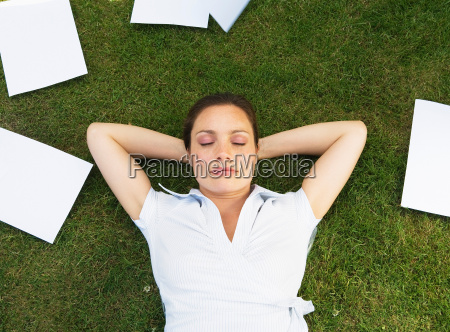 business woman resting on grass