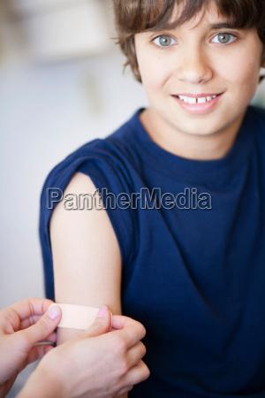 plasterbandage put on smiling young boy
