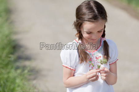 young girl playing with grass