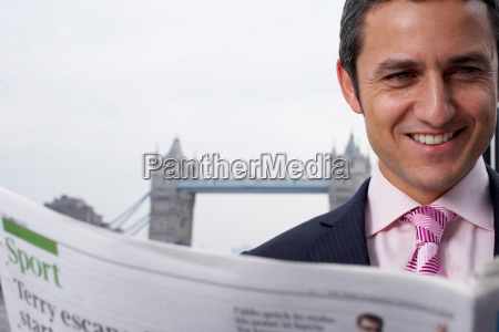 business man reading news paper outside