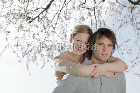 couple hugging under cherry blossom tree