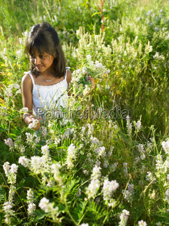girl sitting in field of flowers