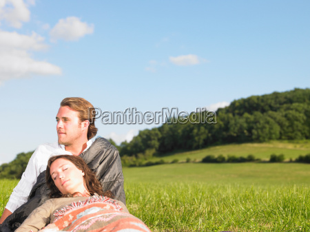 young people lying in field