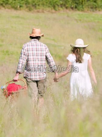 couple in hats walking through meadow