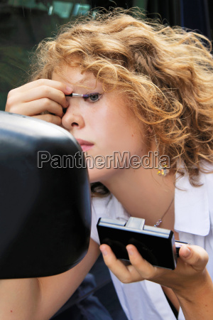 woman applying makeup in car mirror