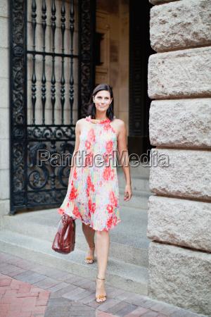 mujer sonriente caminando por la calle