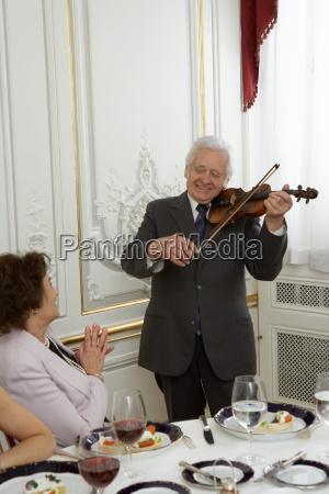 senior adult man playing violin to