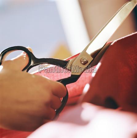 close up of woman cutting fabric