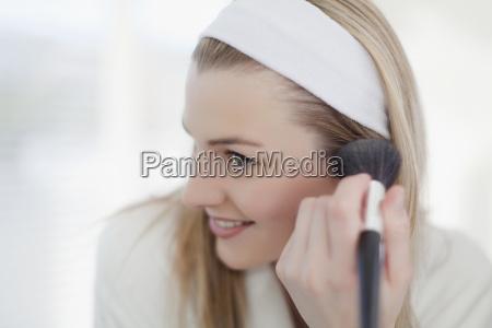 smiling woman applying makeup