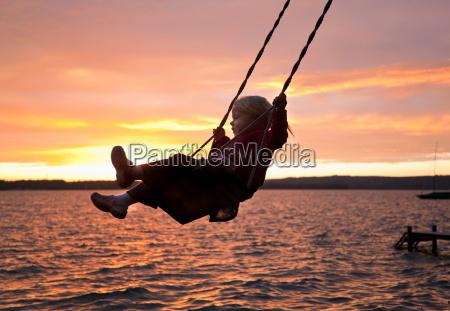 girl swinging by lake