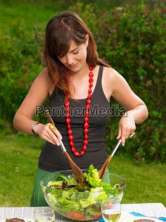 young woman tossing a salad