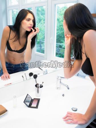 woman, applying, makeup, in, bathroom - 18422582