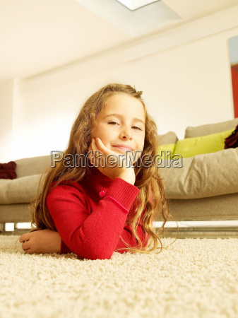 girl lying on rug looking