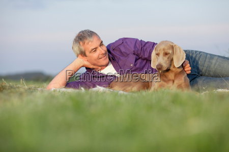man with dog lying on the