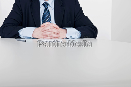 man sitting hands clasped