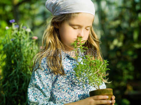 young female smelling a herb plant