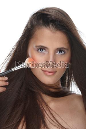 woman applying blusher to her cheeks