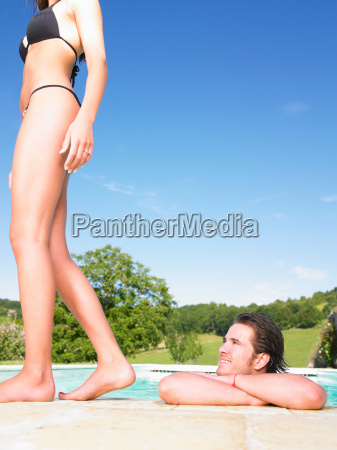 man in pool admiring young woman