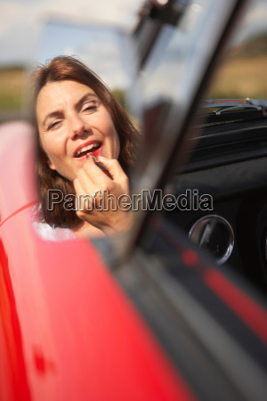 woman applying lipstick in cars mirror