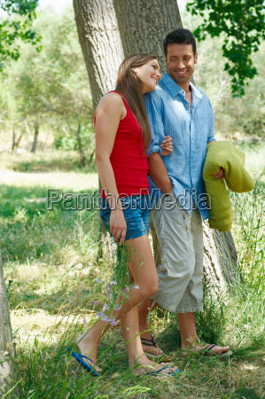 young couple walking together in forest