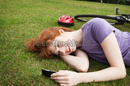 woman laying in grass texting