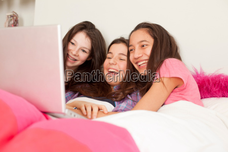 teenage girls sitting in bed with