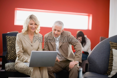 business people using laptop in lounge