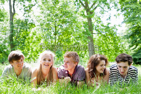 teenagers laying in grass in park