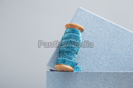 wooden reel of sparkly blue ribbon
