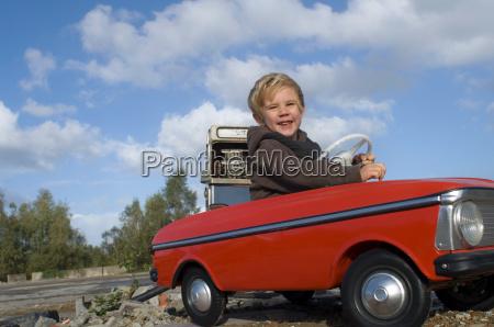 a boy in a toy car
