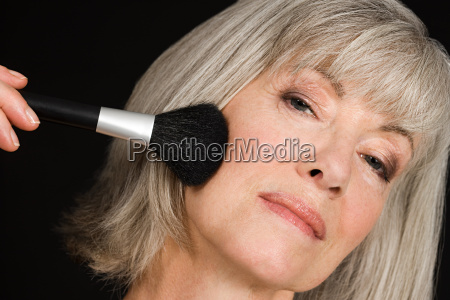 senior woman applying make up