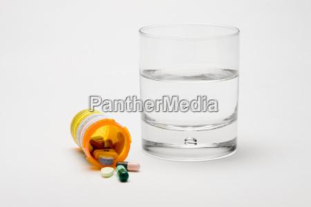 tabletas y un vaso de agua