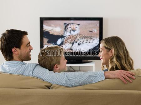 una familia viendo television y hablando