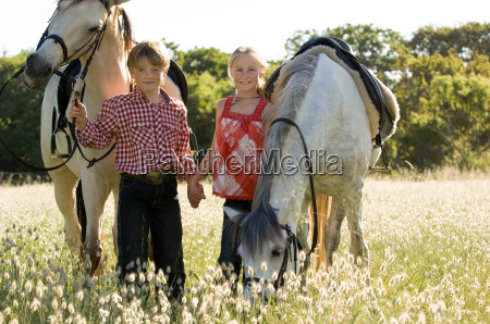 a boy and girl with horses