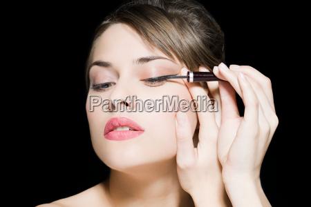 mujer aplicando delineador de ojos