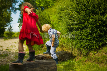 boy and girl stepping on logs