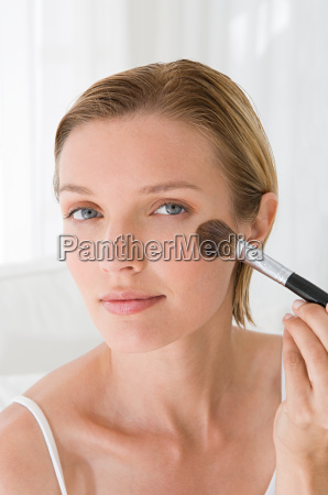 a young woman applying blusher